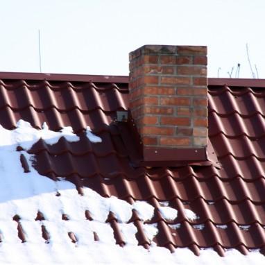 Кирпичная труба дымоход в металлочерепичной крыше зимой